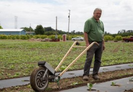 Michael McGowen, Founder of Carts and Tools in the field with a prototype Solis wheel hoe
